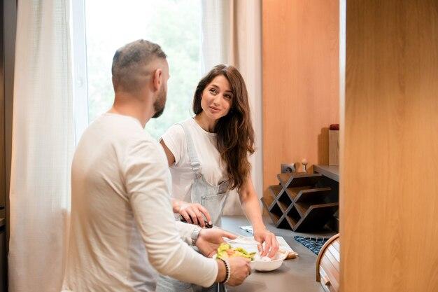 Heureuse jeune famille debout sur une cuisine lumineuse, se regardant et cuisinant ensemble