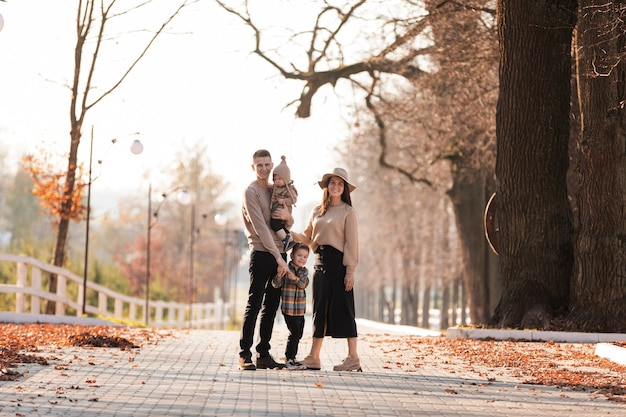 Heureuse jeune famille avec deux petits enfants marchant et s'amusant dans le parc d'automne aux beaux jours
