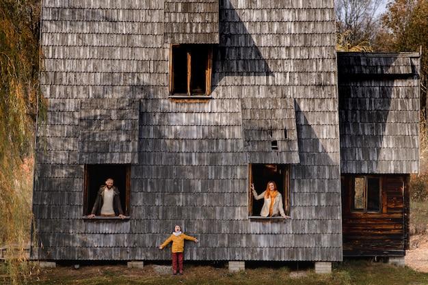 Heureuse jeune famille furtivement par les fenêtres d'une grande maison en bois. le concept d'acheter une maison, de louer une maison, pour une famille