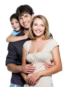 Heureuse jeune famille avec joli enfant posant sur un espace blanc