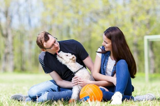 Heureuse jeune famille jouant avec un chien léchant son propriétaire en signe d'affection