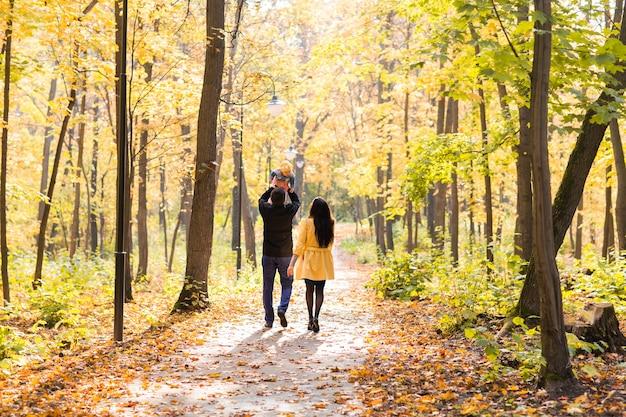 Heureuse jeune famille avec leur fille, passer du temps en plein air dans le parc de l'automne