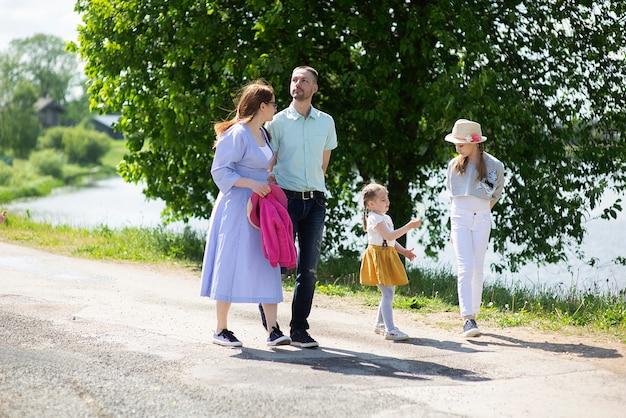 Heureuse jeune famille marchant sur le trottoir du village