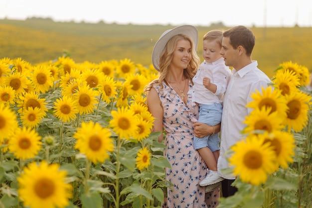 Heureuse jeune famille, mère père et fils, sourient, tenant et serrant dans le champ de tournesol