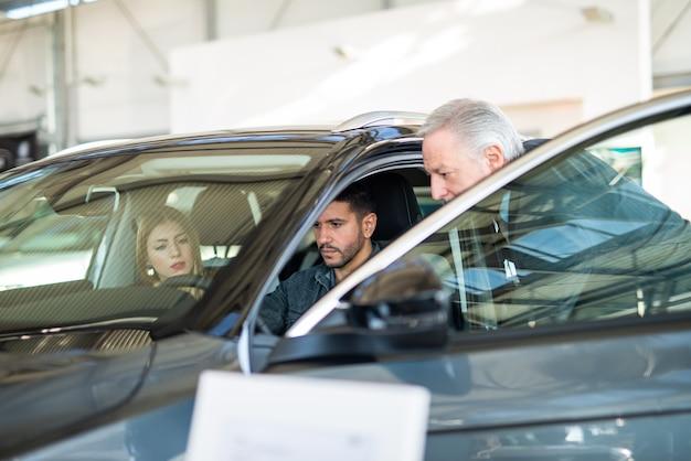 Heureuse jeune famille parlant au vendeur et choisissant leur nouvelle voiture dans une salle d'exposition