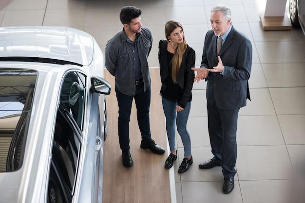 Heureuse jeune famille parlant au vendeur et choisissant sa nouvelle voiture dans une salle d'exposition