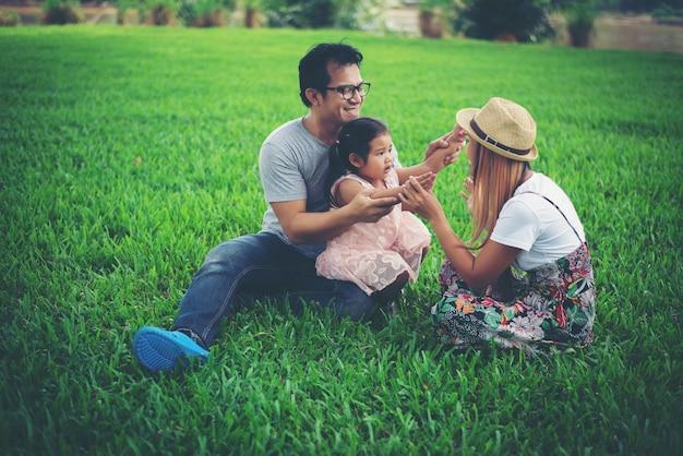 Heureuse jeune famille passer du temps dans le parc, père mère et fille jouant sur l'herbe