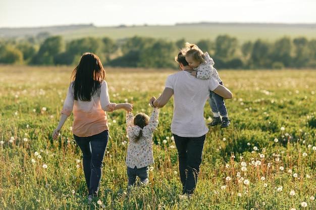Heureuse jeune famille, passer du temps ensemble à l'extérieur dans la nature verdoyante.
