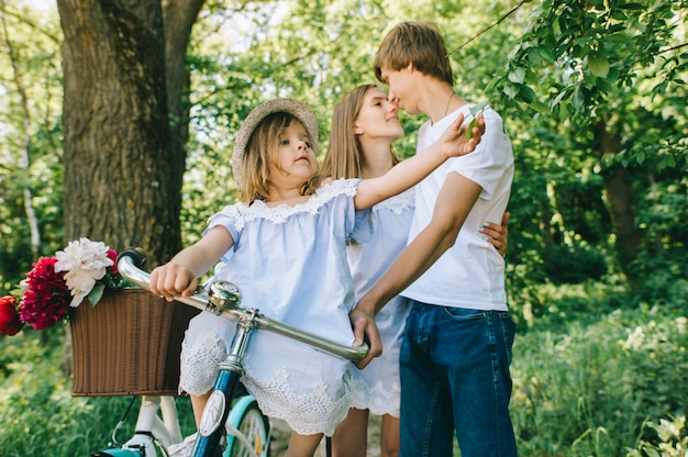 Heureuse jeune famille, passer du temps ensemble à l'extérieur. père, mère et leur enfant dans le parc vert sur un pique-nique