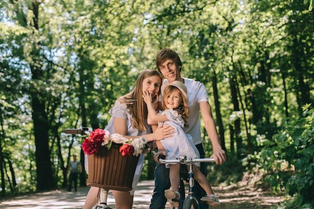 Heureuse jeune famille, passer du temps ensemble à l'extérieur. père mère et leur enfant dans le parc vert sur un pique-nique