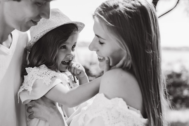 Heureuse jeune famille passer du temps ensemble à l'extérieur. père mère et leur enfant dans le parc vert s'amusent