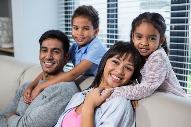 Heureuse jeune famille posant ensemble sur le canapé