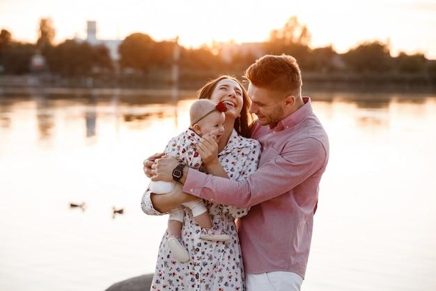 Heureuse jeune famille près du lac, de l'étang. famille profitant de la vie ensemble au coucher du soleil. les gens s'amusent dans la nature. look familial. mère, père, enfant souriant tout en passant du temps libre à l'extérieur