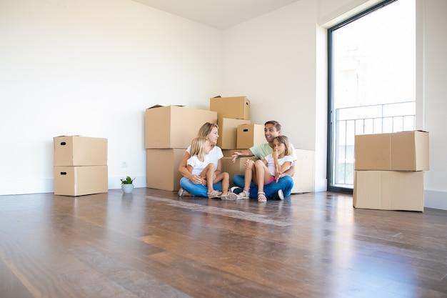 Heureuse jeune famille se détendre sur le sol pendant le déménagement et parler