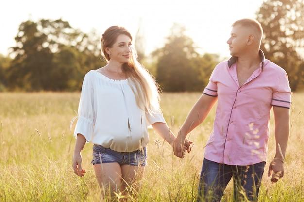 Heureuse jeune famille se tenir la main et traverser le champ d'été, se regarder avec amour. la femme enceinte passe du temps libre avec son mari, respire l'air frais. romance, amour, concept de relation