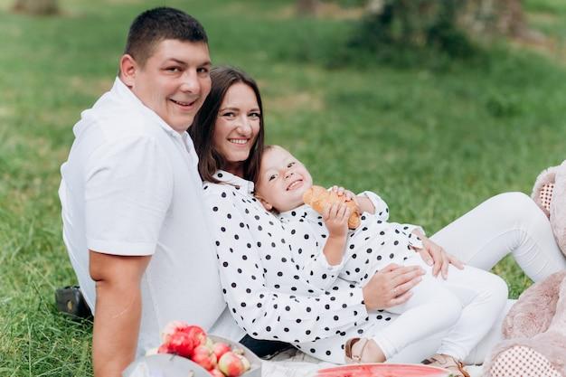 Heureuse jeune famille souriante sur pique-nique dans le parc à la journée d'été. le concept de vacances d'été. fête des pères, des mères et des bébés. passer du temps ensemble. mise au point sélective