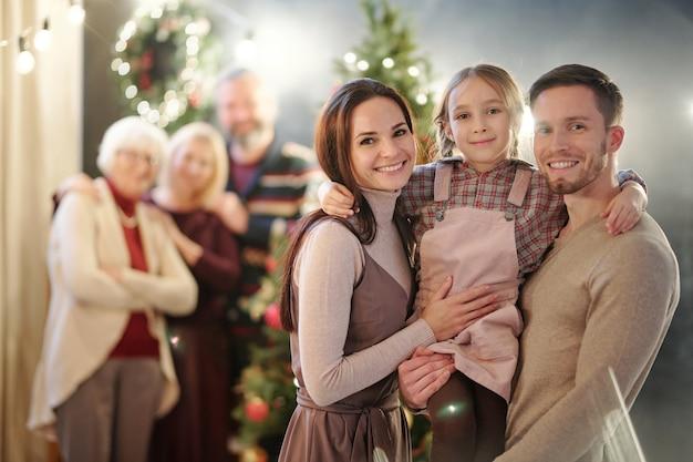 Heureuse jeune famille de trois personnes debout avec des adultes matures par arbre de noël