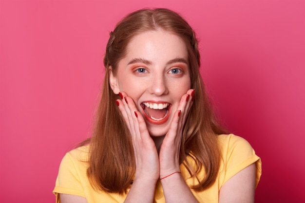 Heureuse jeune femme adorable crie quelque chose en triomphe, a de merveilleuses nouvelles, veut partager son bonheur