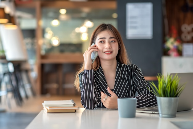 Heureuse jeune femme d'affaires asiatique travaillant sur ordinateur portable et parler sur smartphone.