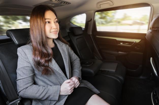 Heureuse jeune femme d'affaires assise sur le siège arrière de la voiture