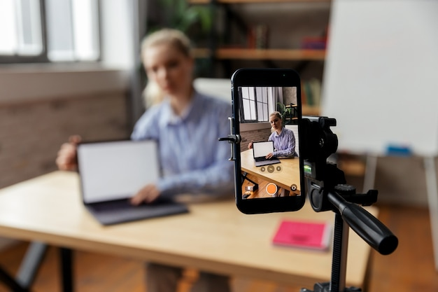 Heureuse jeune femme d'affaires intelligente filmant un tutoriel éducatif ou partageant des compétences professionnelles. concentrez-vous sur l'écran du téléphone. photo de haute qualité