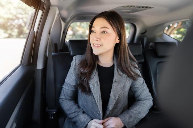 Heureuse jeune femme d'affaires pensant et regardant par la fenêtre alors qu'elle était assise sur le siège arrière de la voiture