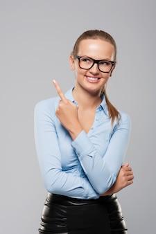 Heureuse jeune femme d'affaires pointant son doigt sur l'espace de copie