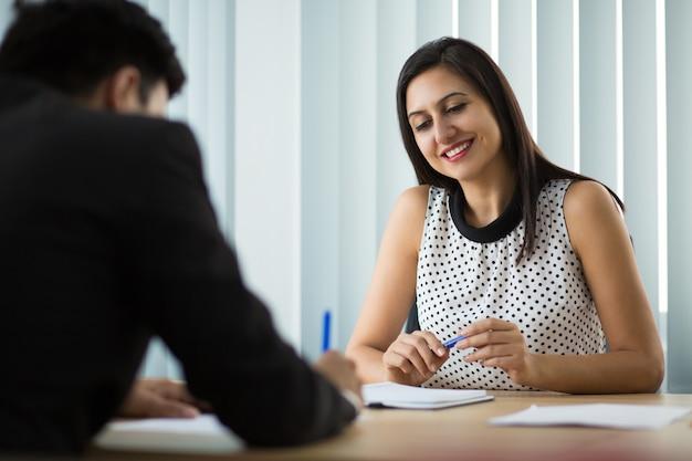 Heureuse jeune femme d'affaires regardant un partenaire signer un contrat