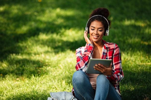 Heureuse jeune femme africaine assise à l'extérieur dans le parc.