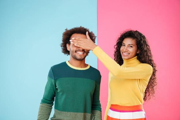 Heureuse jeune femme africaine couverte les yeux de son petit ami à la main sur fond coloré