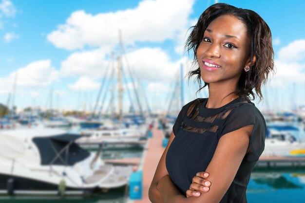 Heureuse jeune femme africaine debout avec les bras croisés