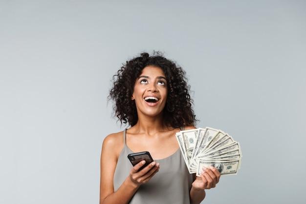 Heureuse jeune femme africaine debout isolée, tenant des tas de billets d'argent, à l'aide de téléphone mobile
