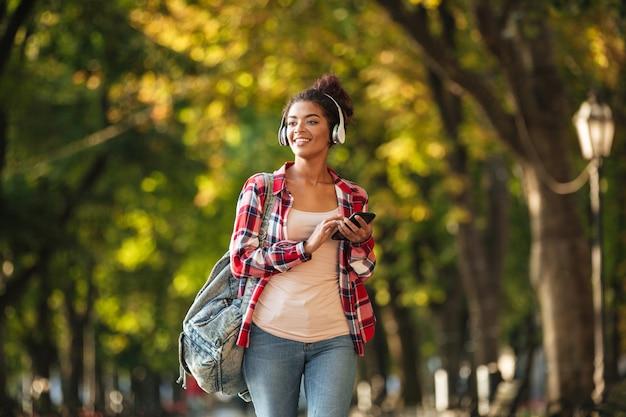 Heureuse jeune femme africaine marchant à l'extérieur dans le parc