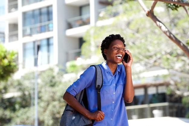 Heureuse jeune femme africaine rire avec un téléphone cellulaire à l'extérieur