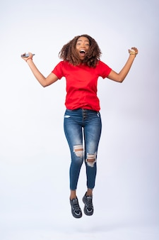 Heureuse jeune femme africaine sautant d'excitation, tenant son téléphone