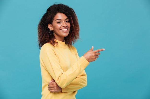 Heureuse jeune femme africaine vêtue d'un pull chaud pointant.