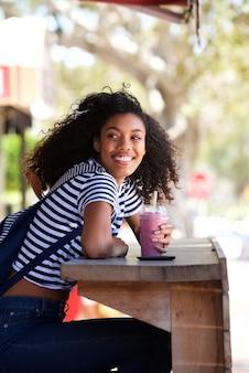 Heureuse jeune femme afro-américaine assis à l'extérieur en tenant une boisson smoothy