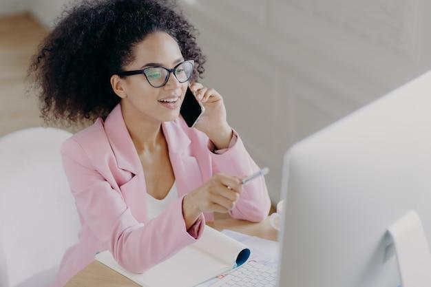 Heureuse jeune femme afro-américaine discute de nouvelles, pointe avec un stylo à l'écran sur ordinateur,