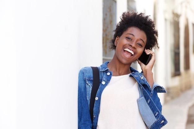 Heureuse jeune femme afro-américaine parlant au téléphone mobile à l'extérieur