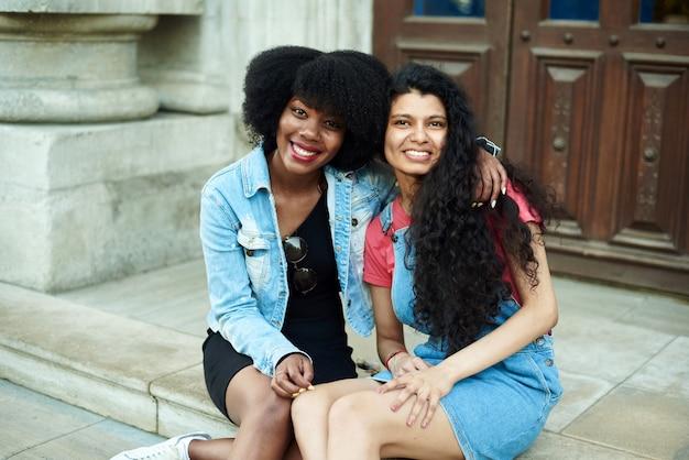 Heureuse jeune femme afro-américaine souriante, embrassant des copines indiennes et regardant la caméra. concept d'amitié multinationale.