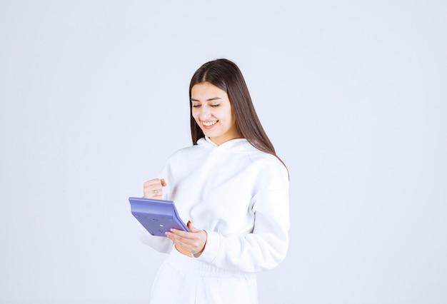 Heureuse jeune femme à l'aide d'une calculatrice sur fond blanc-gris.