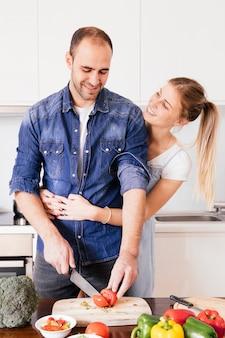 Heureuse jeune femme aimant son mari couper les légumes avec un couteau dans la cuisine