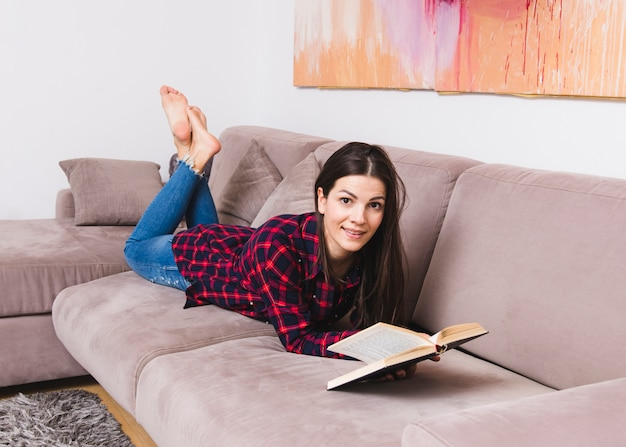 Heureuse jeune femme allongée sur un canapé en lisant un livre