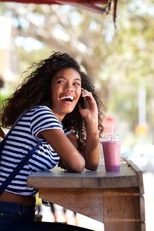 Heureuse jeune femme américaine africana rire et parler au téléphone portable au café