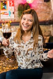 Heureuse jeune femme appréciant la fête tenant un verre à vin