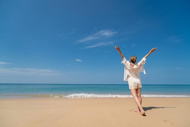 Heureuse jeune femme appréciant la liberté avec les mains ouvertes sur la mer.