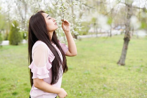 Heureuse jeune femme appréciant les odeurs dans un jardin fleuri