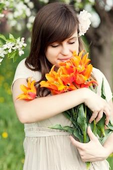 Heureuse jeune femme appréciant le parfum des fleurs