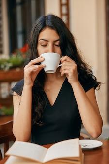 Heureuse jeune femme arabe, boire du café dans un café