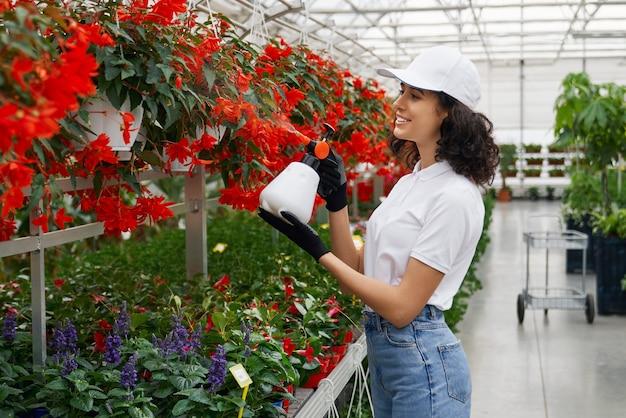 Heureuse jeune femme arrosant de belles fleurs rouges